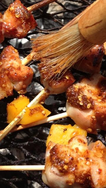 rubbing seasoning on grilled chicken