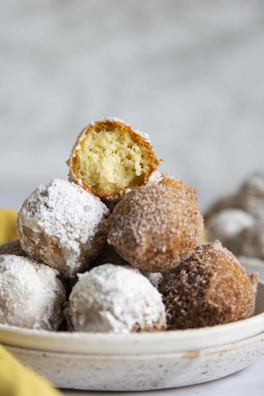A tower of donut holes with one half eaten on top.