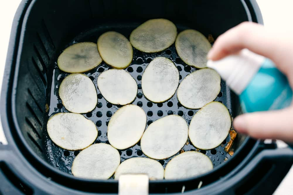 Spritzing sliced potatoes in air fryer with oil.