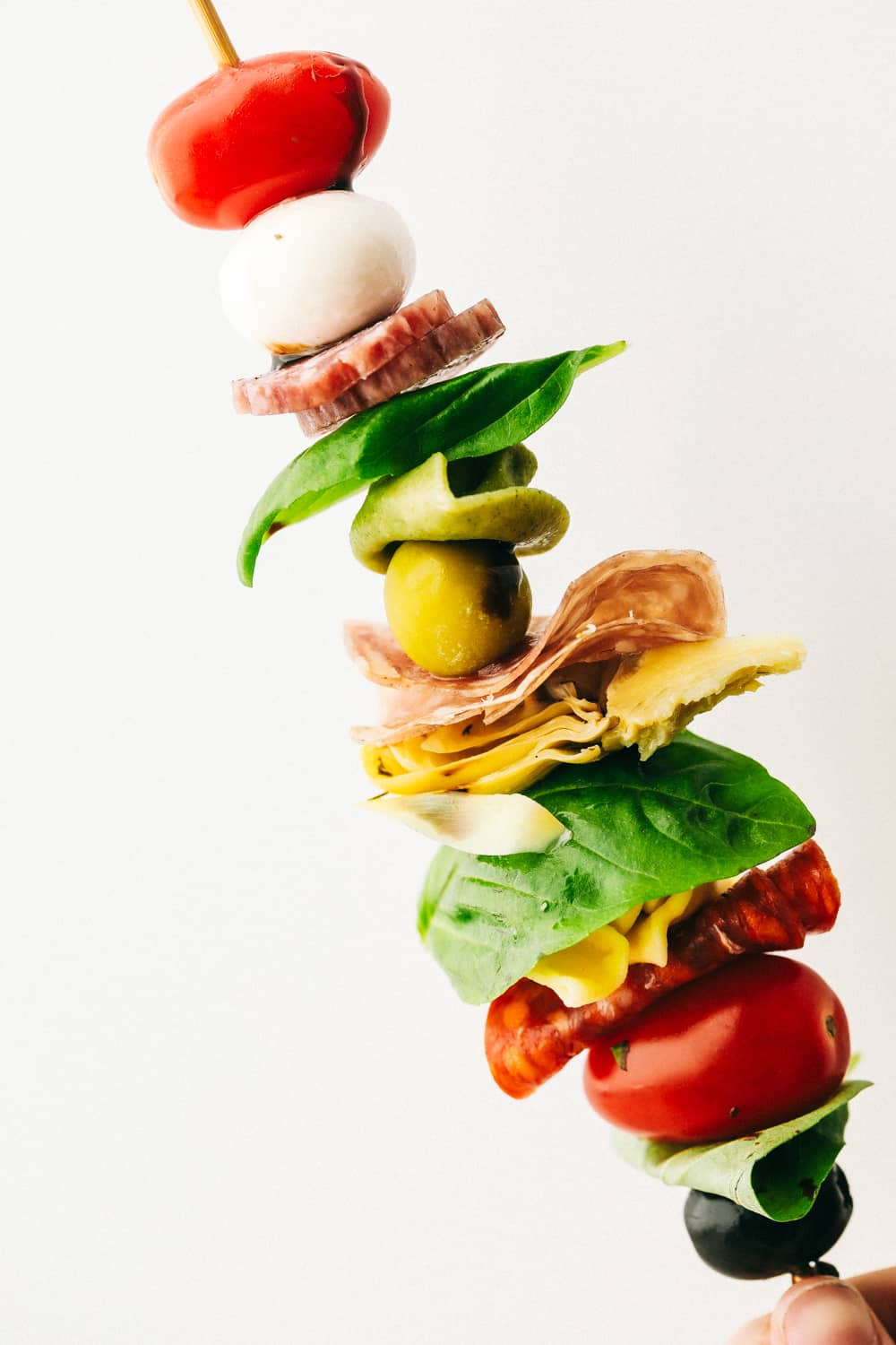 Up close look at an antipasto skewer layered with ingredients.
