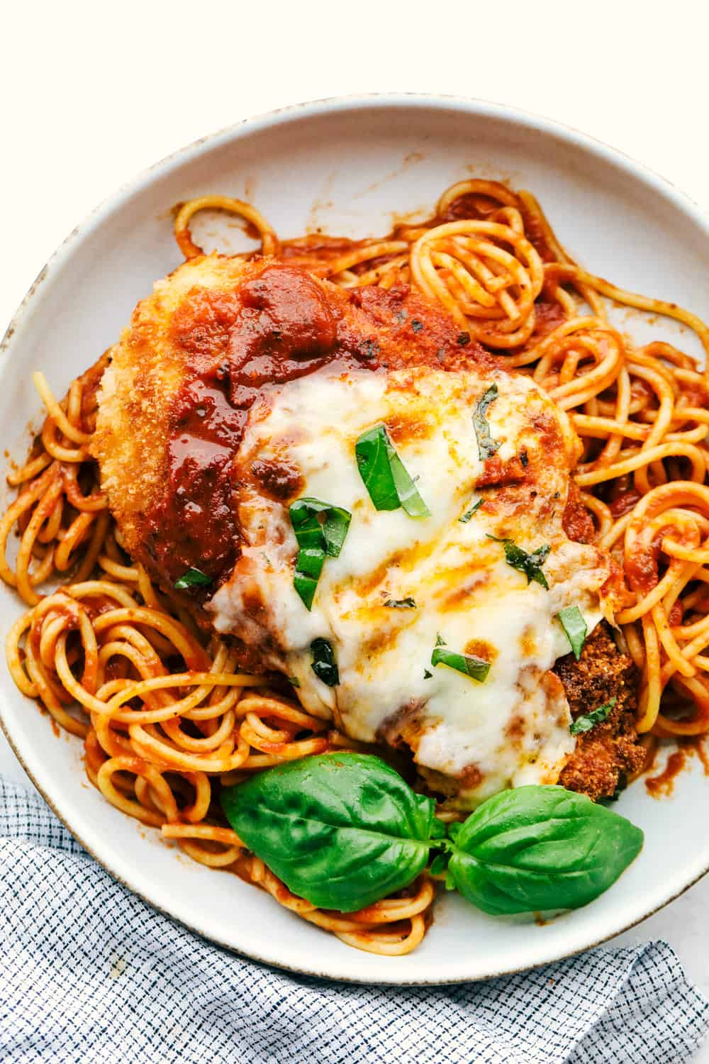 Parmesan chicken on a bed of spaghetti with marinara sauce.