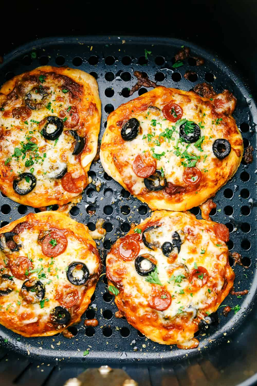 Perfectly baked air fryer biscuit pizzas.