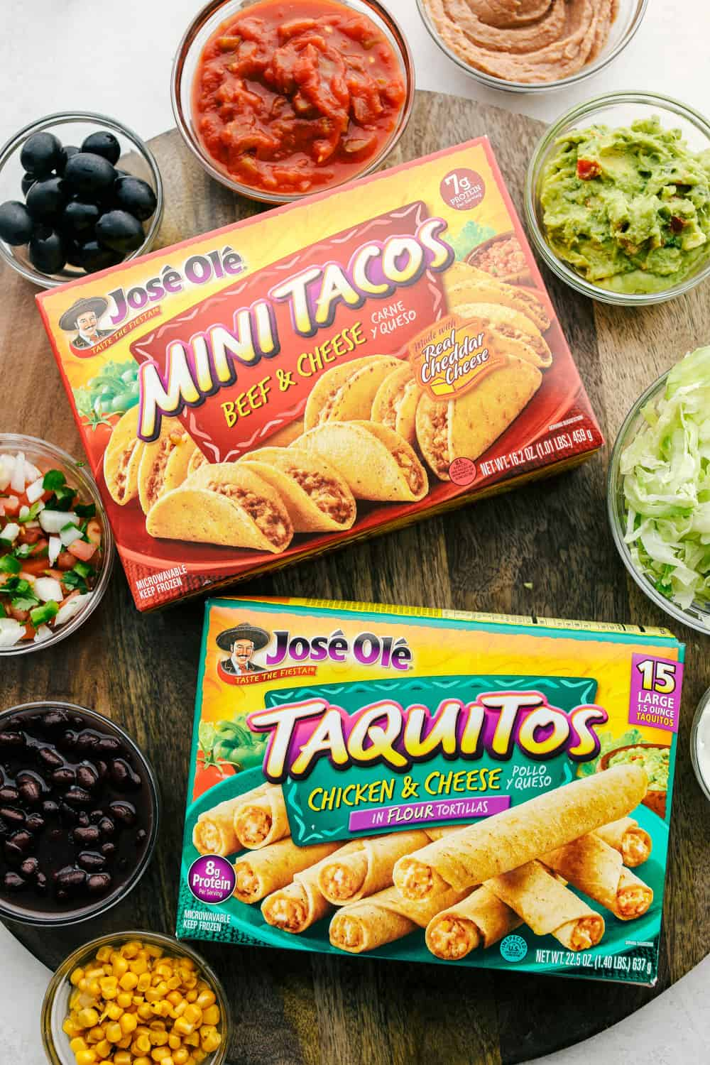 Mini tacos and taquitos in a box with bowls of dips and vegetables.