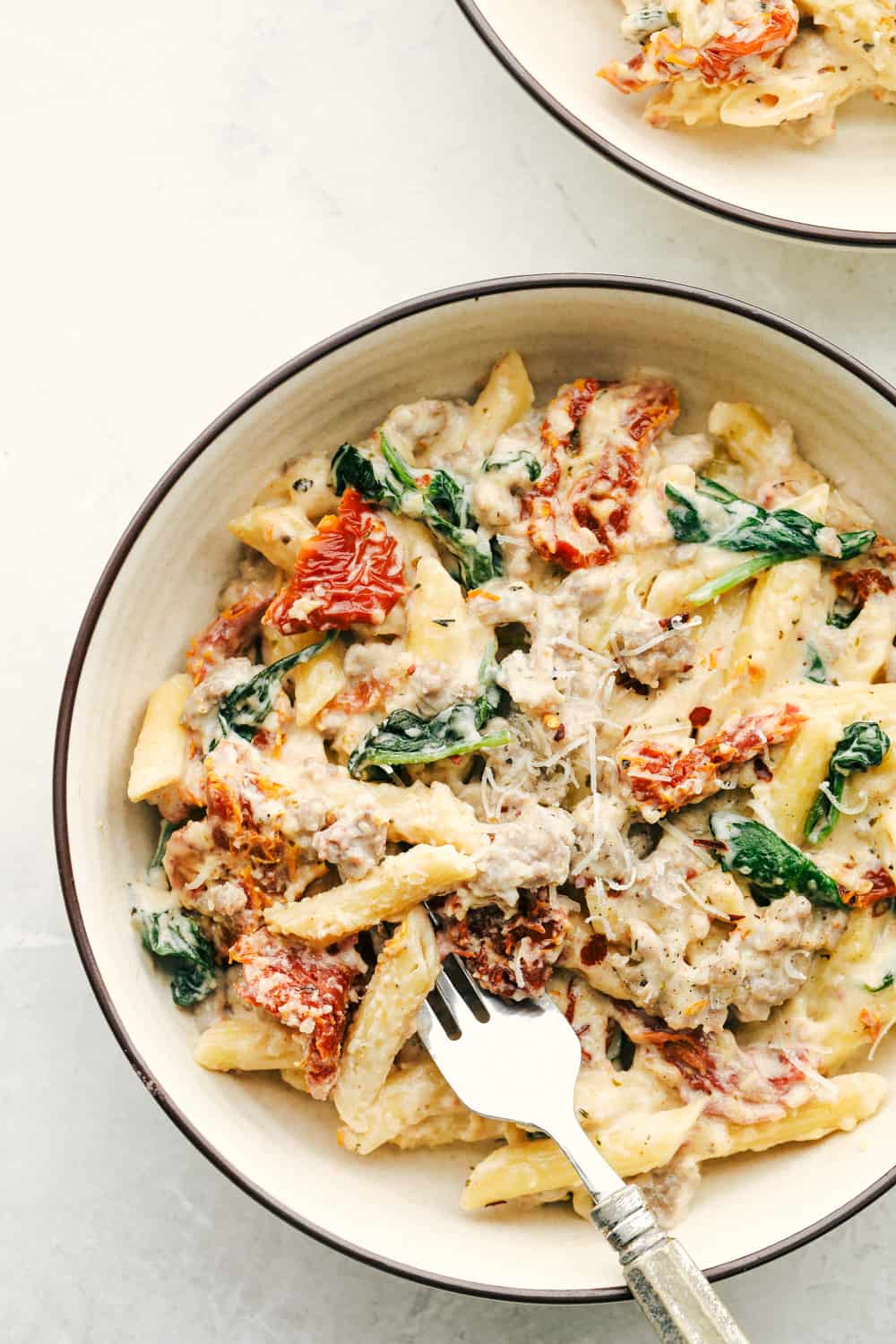 Tuscan sausage pasta in a white bowl with a fork.