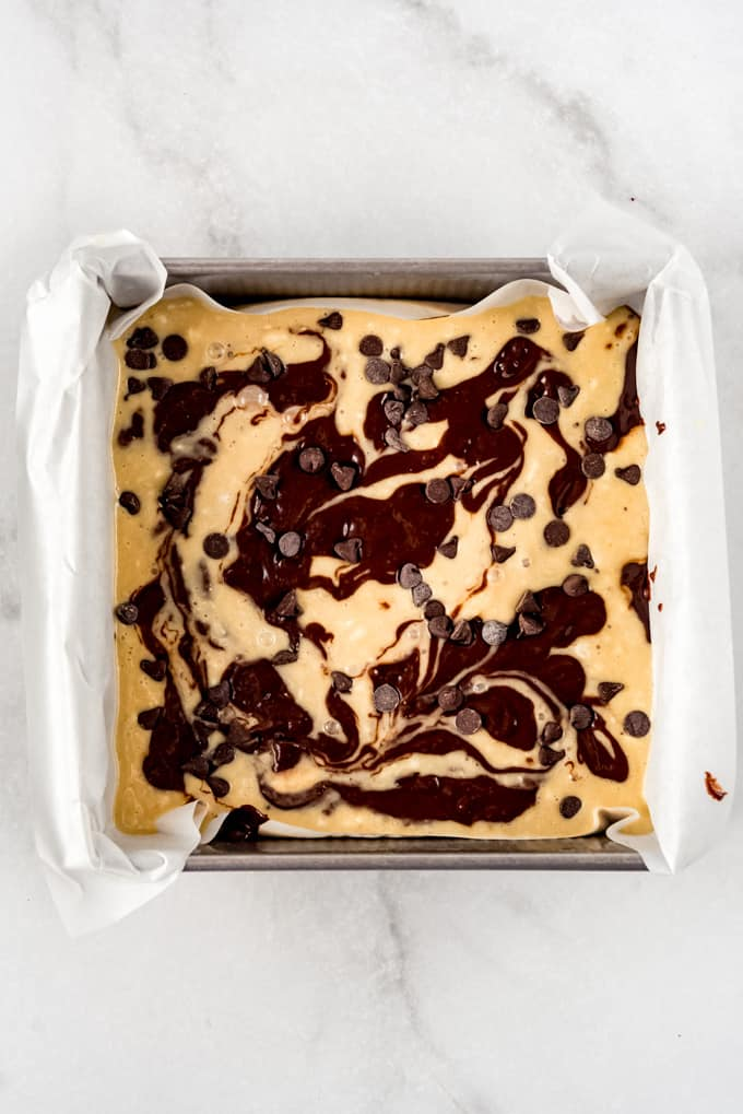 Swirled banana bread and brownie batter in a square pan.