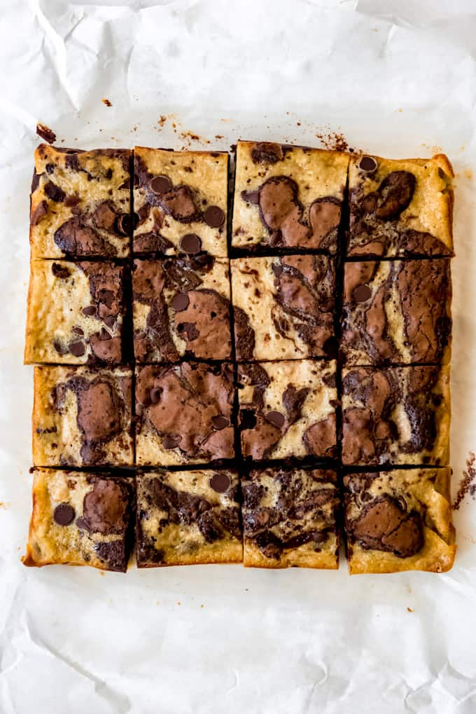 Swirled banana bread brownies cut into squares on parchment paper.