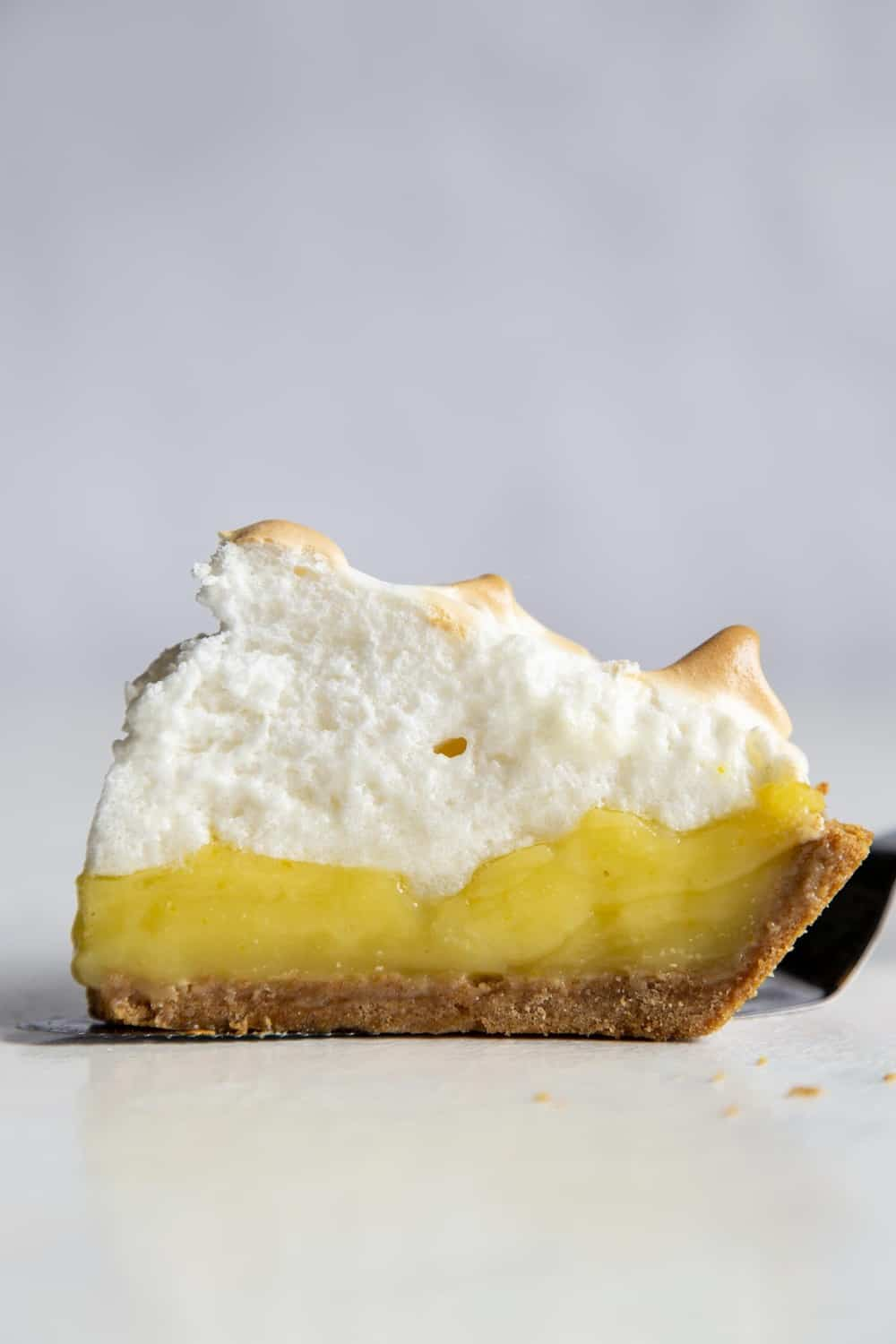 A side view of the layers of lemon and meringue in the slice of pie.