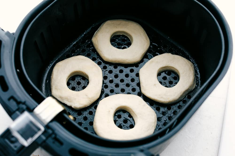 Biscuit donuts in an air fryer basket ready to bake.