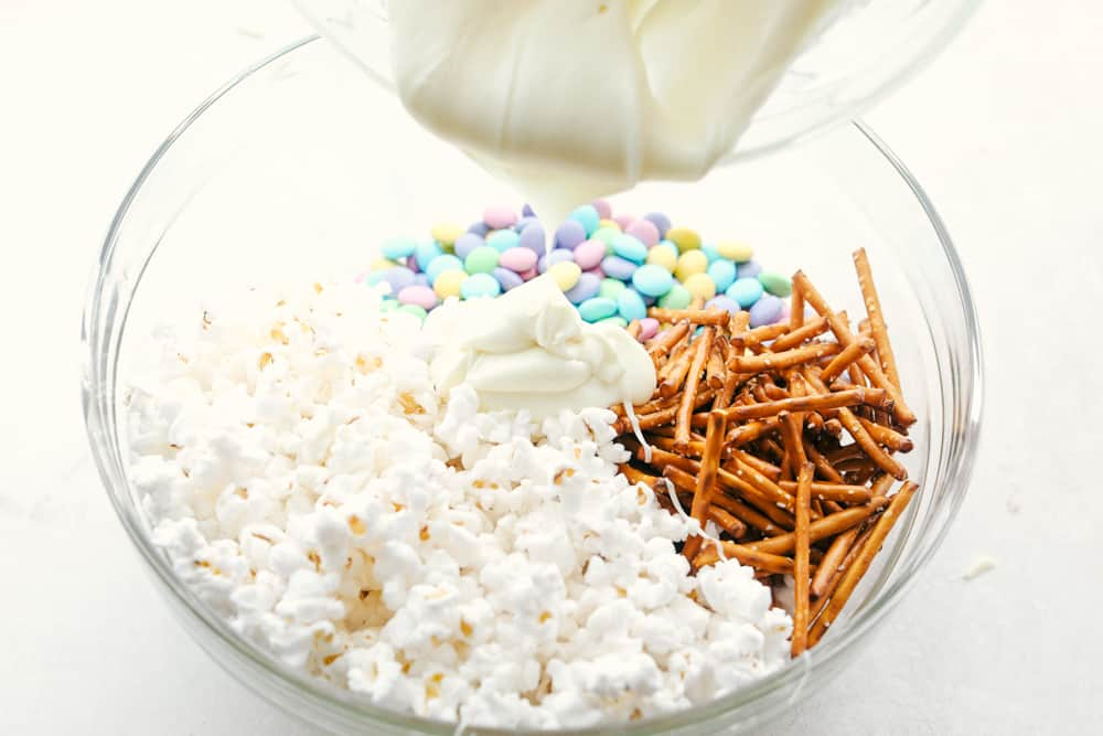Pouring melted white chocolate over popcorn, M&Ms and pretzels.