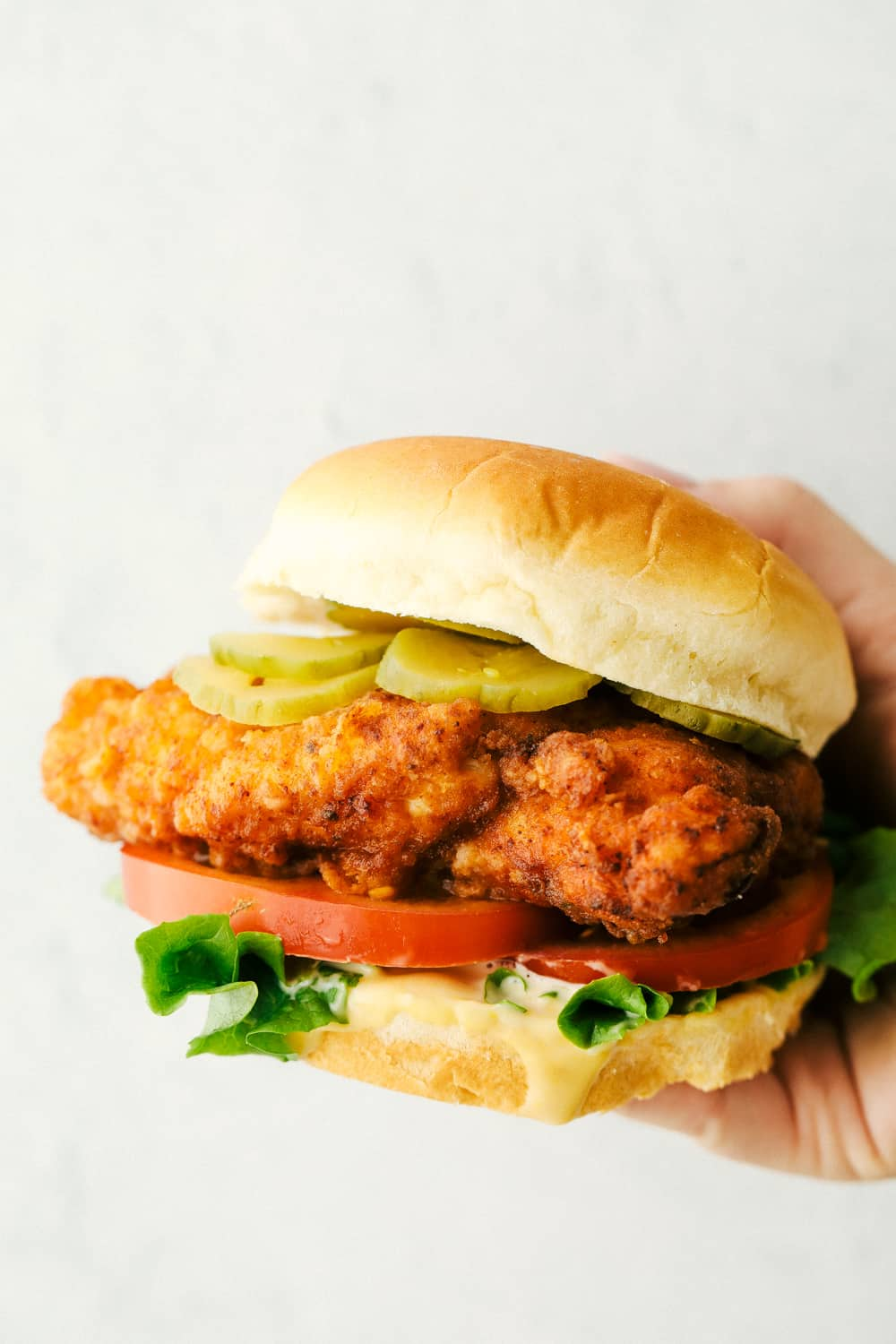 Holding a chicken sandwich with pickles, lettuce and tomatoes.