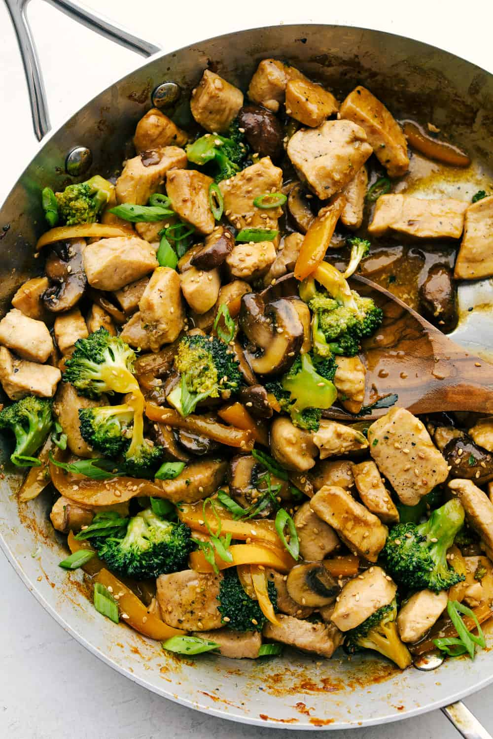 Chicken Garlic stir fry in the pan with broccoli and mushrooms.