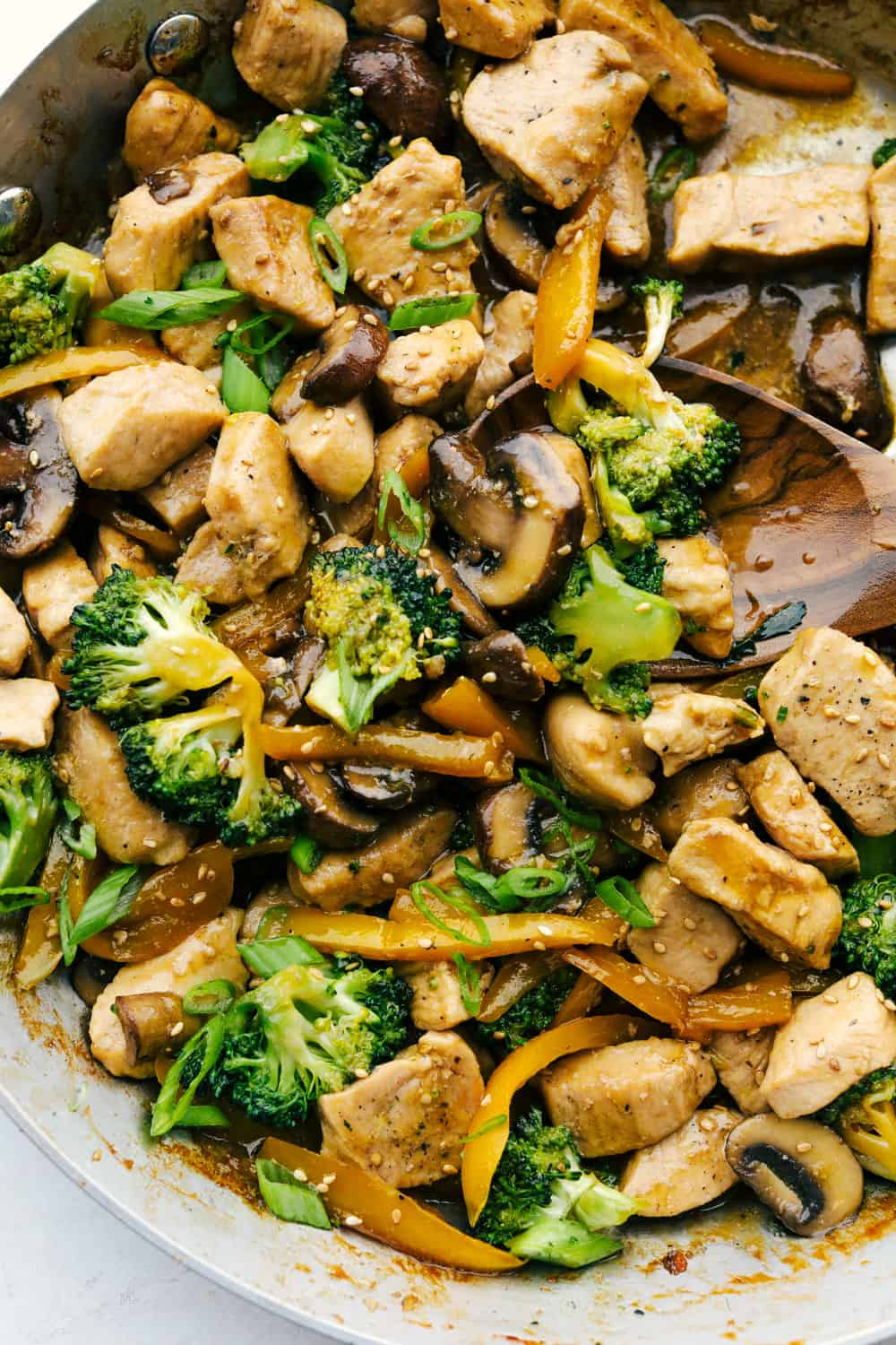 Stirring the chicken, broccoli and mushrooms all together.