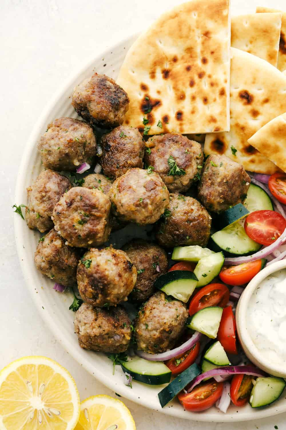 Greek meatballs on a plate with pitas, cucumbers, tomatoes, and tzatziki sauce.