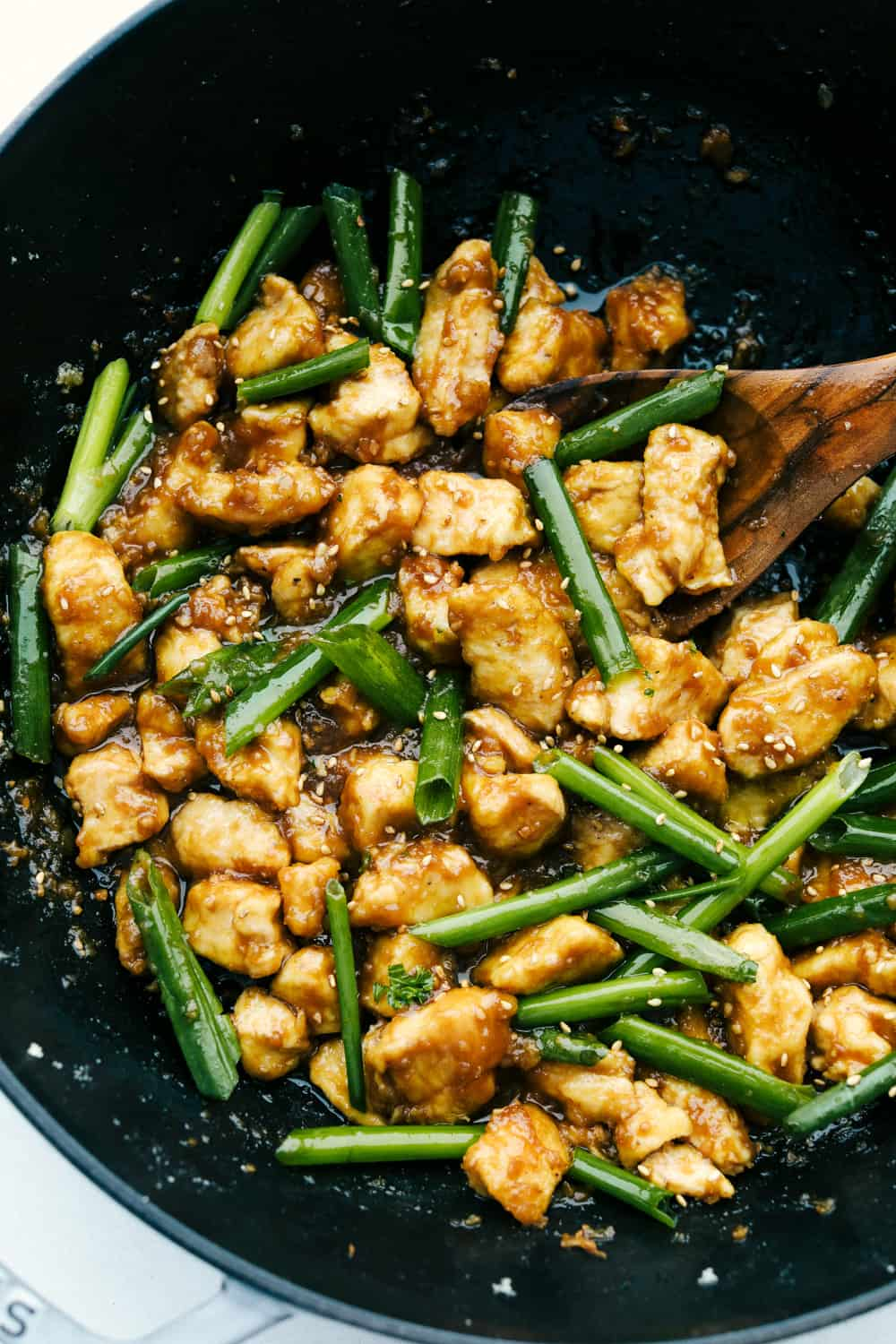 Chicken and green onions sauteed in a wok.