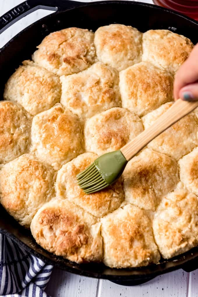 brushing the tops of angel biscuits with melted butter