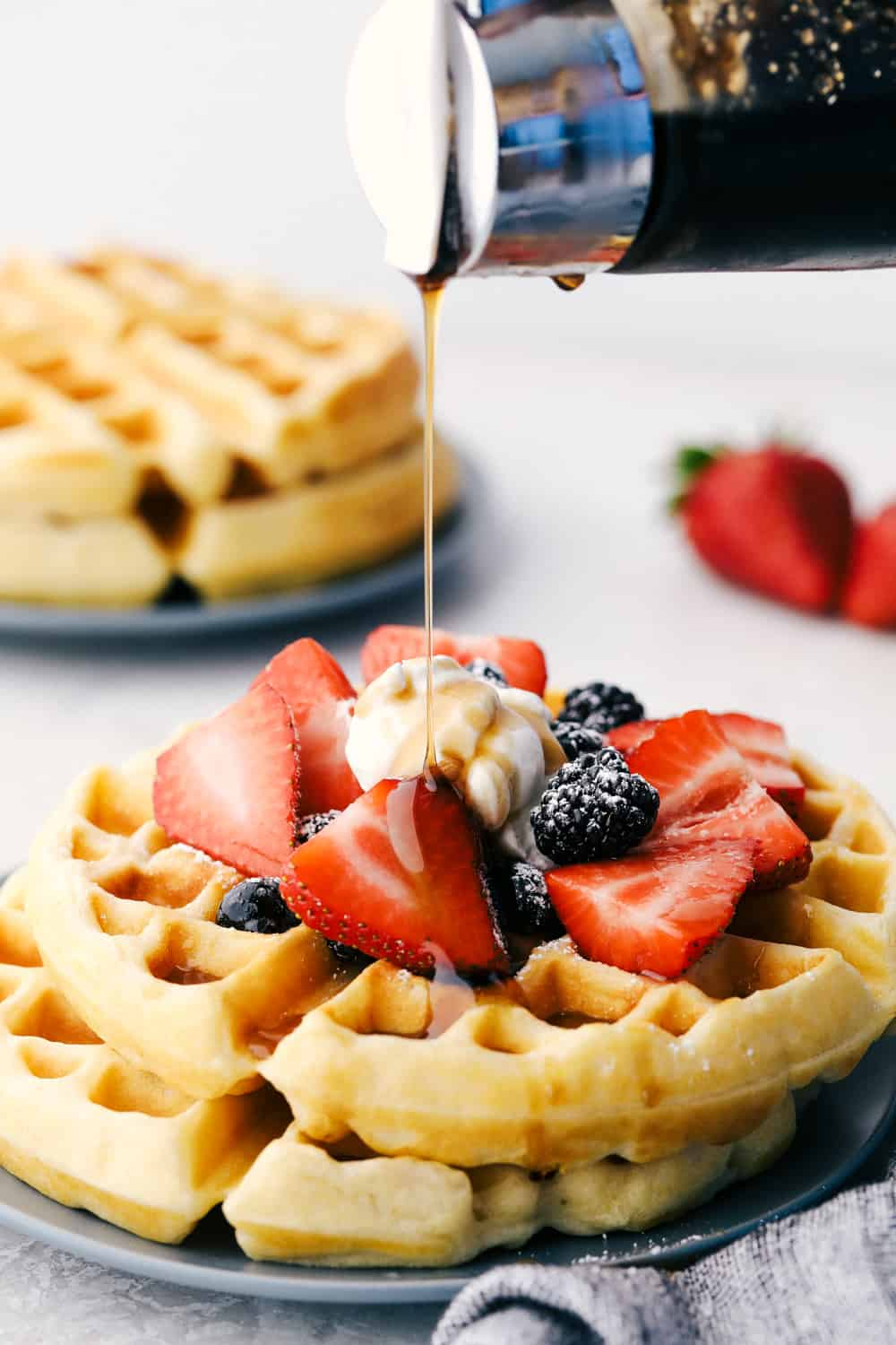 Pouring syrup over waffles with fruit and whipped cream.