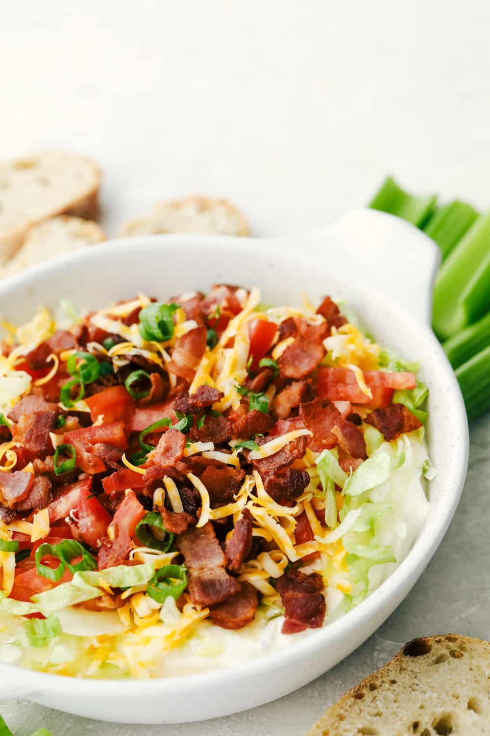 The finished BLT dip in a white bowl with options for dipping.