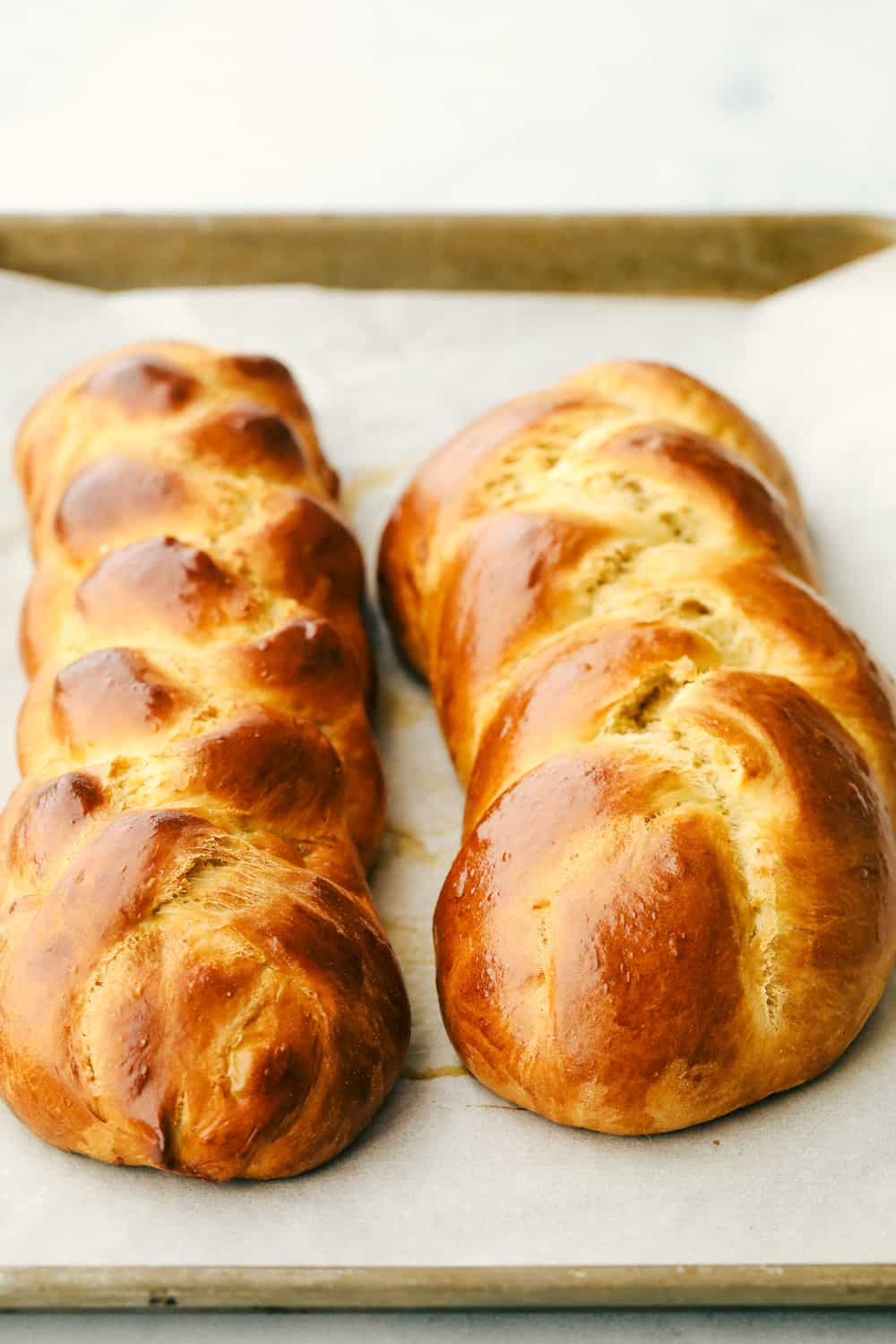 Two baked loaves of Challah golden brown.