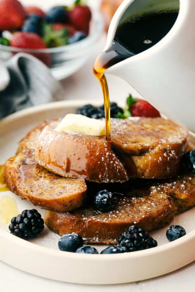 Challah French toast with maple syrup being over it.