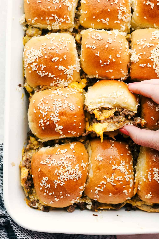 Grabbing a cheeseburger slider out of the pan.