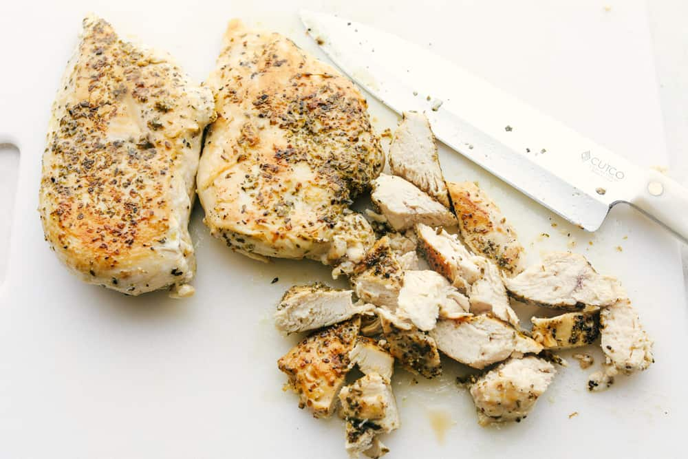 Cutting up cooked chicken.