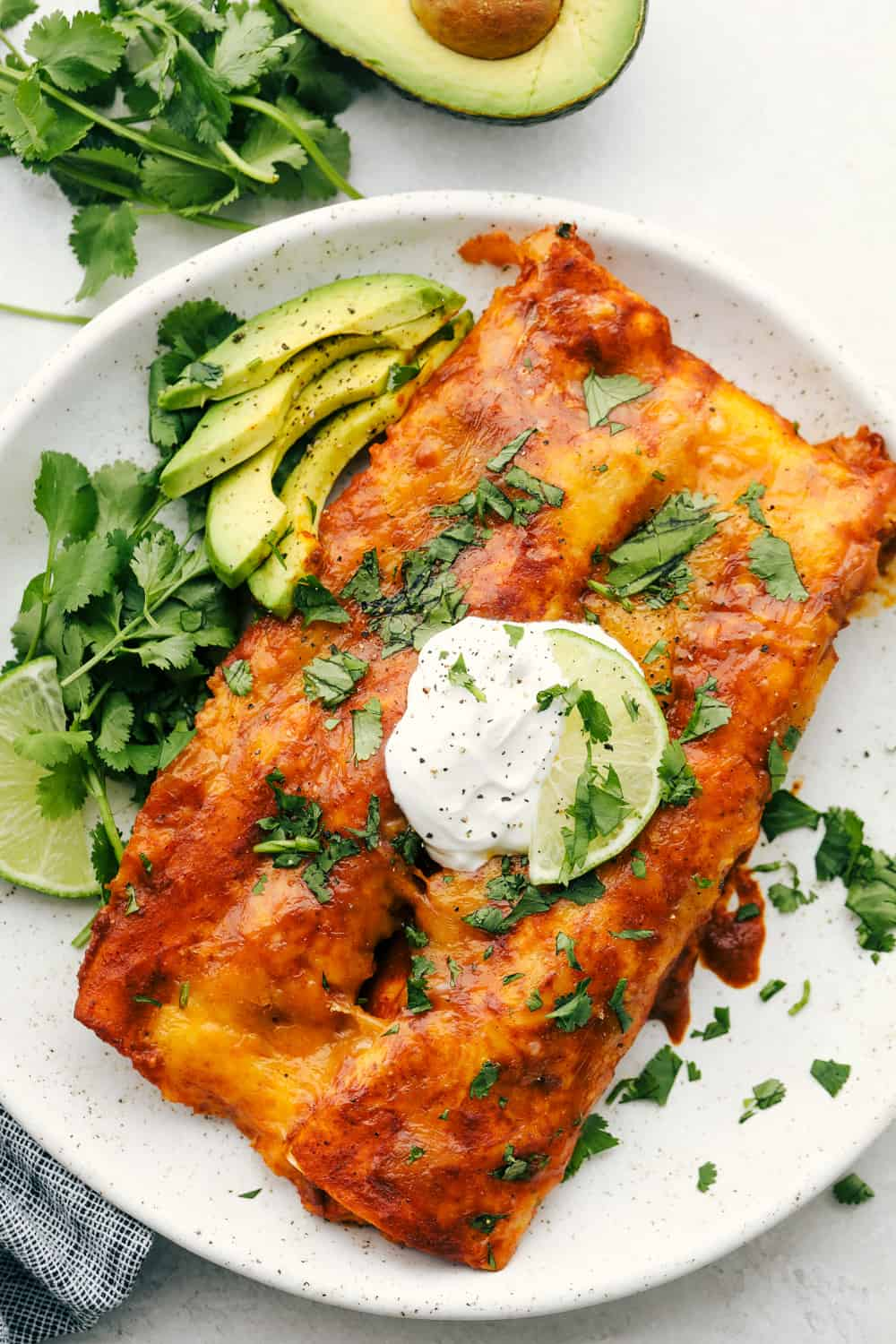 Enchiladas on a plate with sour cream and sliced avocados.
