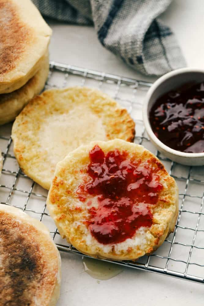 Toasted english muffins on a cooling rack with butter and jam.