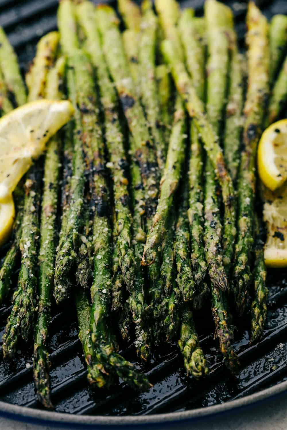 Asparagus on the grill plate with lemon wedges on the side.
