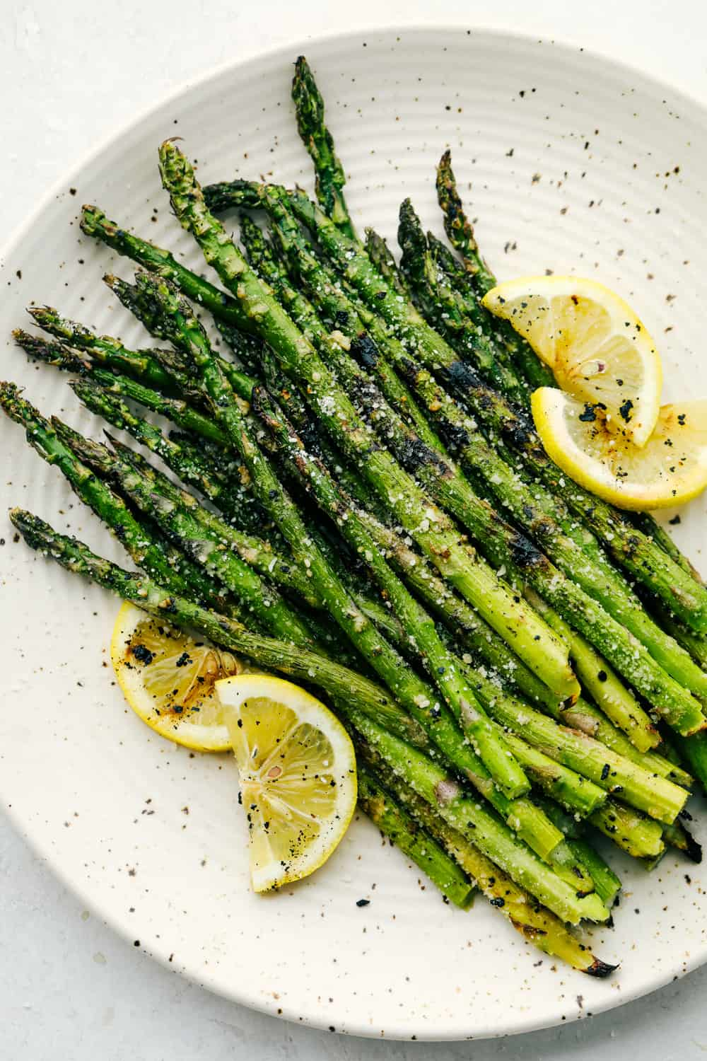 Grilled Asparagus on a white plate garnished with lemon wedges.