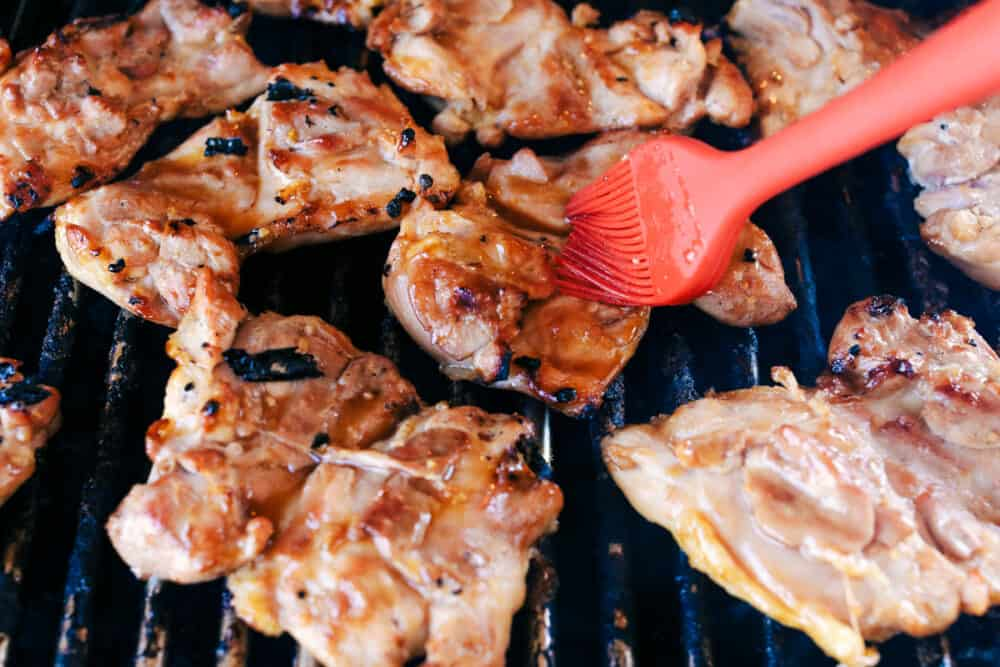 Basting chicken as it grills.