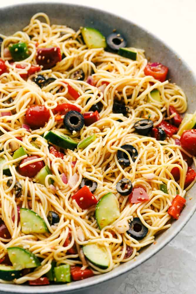 California spaghetti salad in a gray bowl with olives, tomatoes and fresh vegetables.