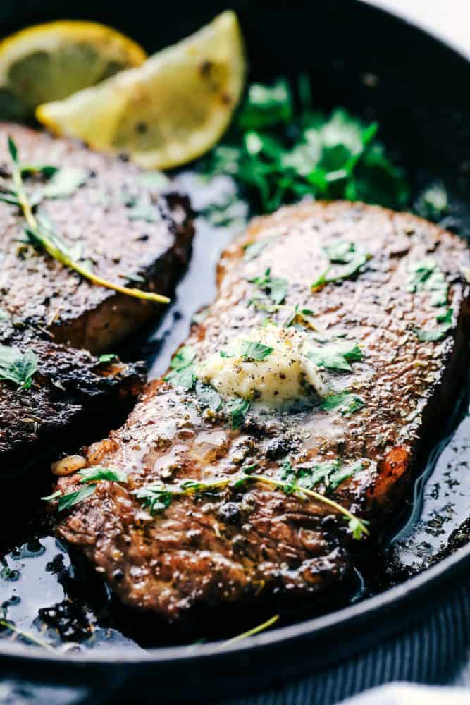 Cooked steak in a skillet with marinade, lemons and garnish on top.