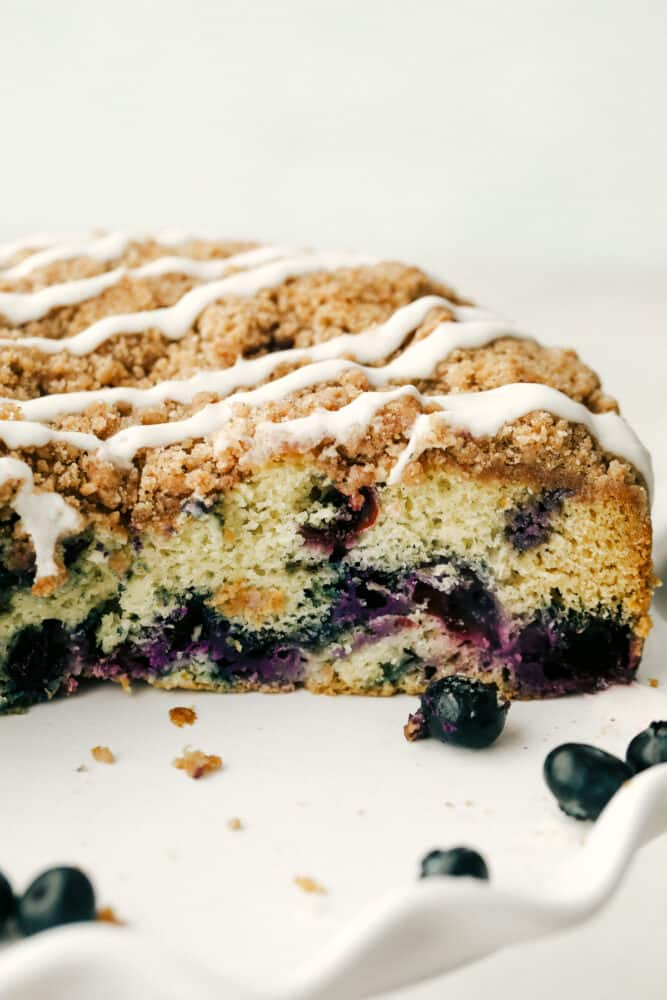 A cross cut of the baked blueberry crumb cake with frosting drizzle.