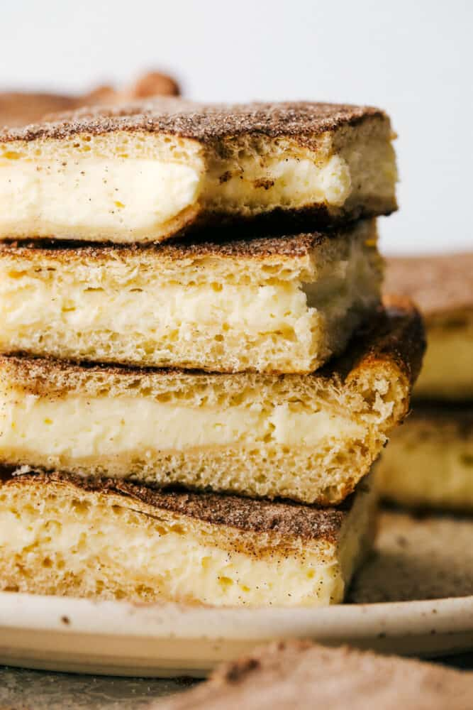 Churro cheesecake bars stacked with a bite out of them.