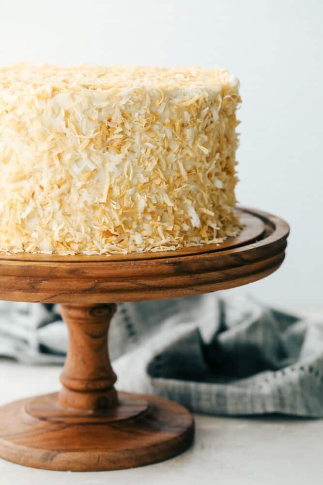 Coconut cake on a pedestal ready to cut.