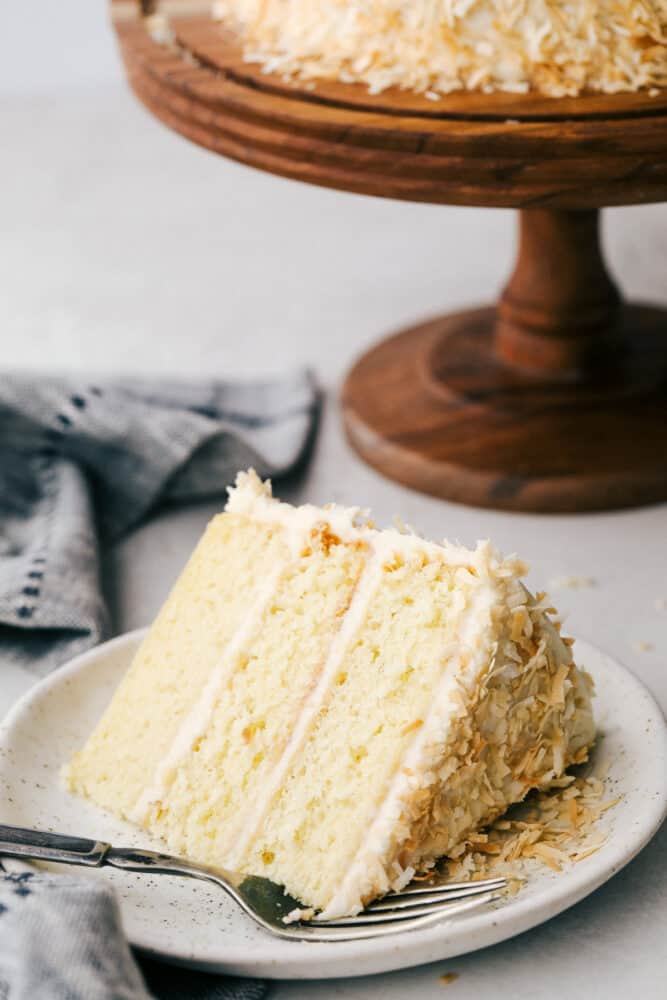 A slice of coconut cake with frosting and toasted coconut on a plate.