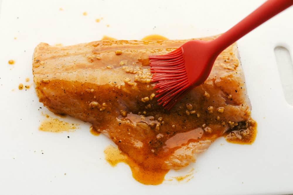Basting the cod with the cajun garlic seasoning.
