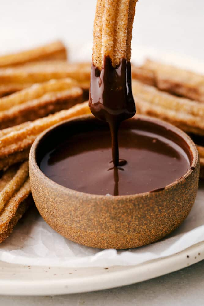 Dipping a churro in chocolate sauce.
