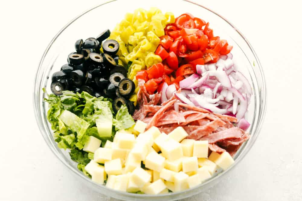 Ingredients for Italian chopped salad in a clear bowl, ready to be mixed.