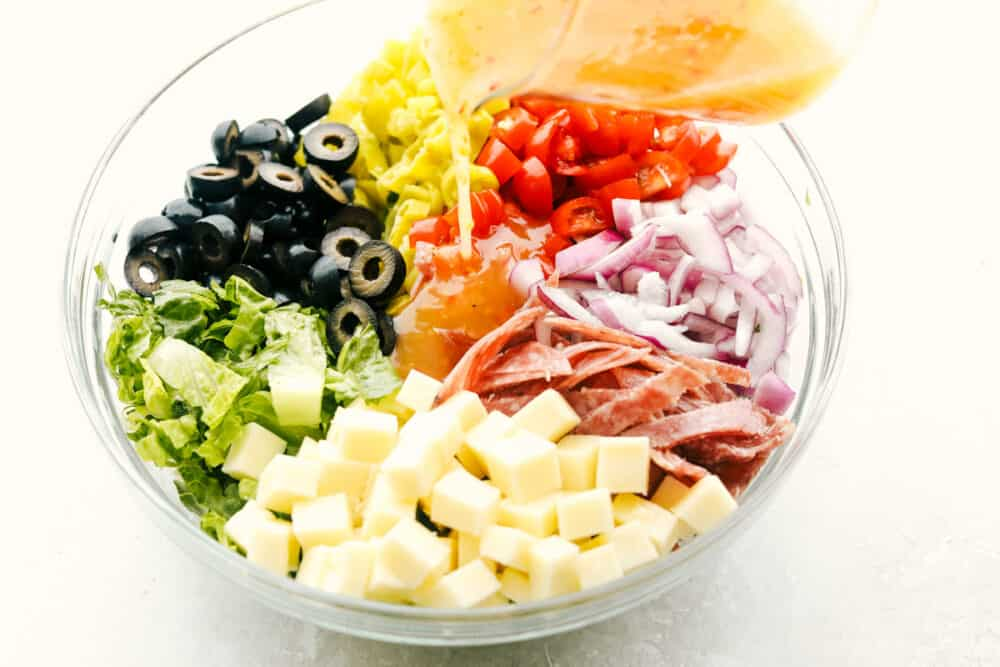 Pouring the dressing over the salad ingredients.