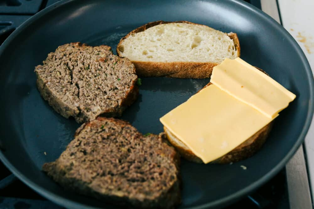 Grilling the meatloaf, and bread topped with cheese.