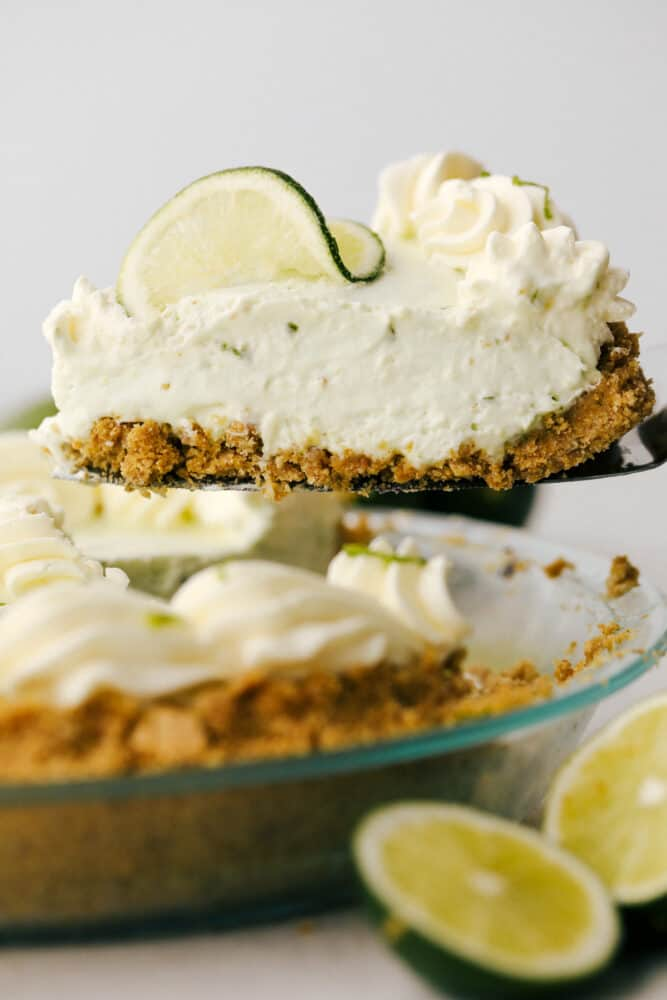 A slice of key lime pie being lifted from the tin.