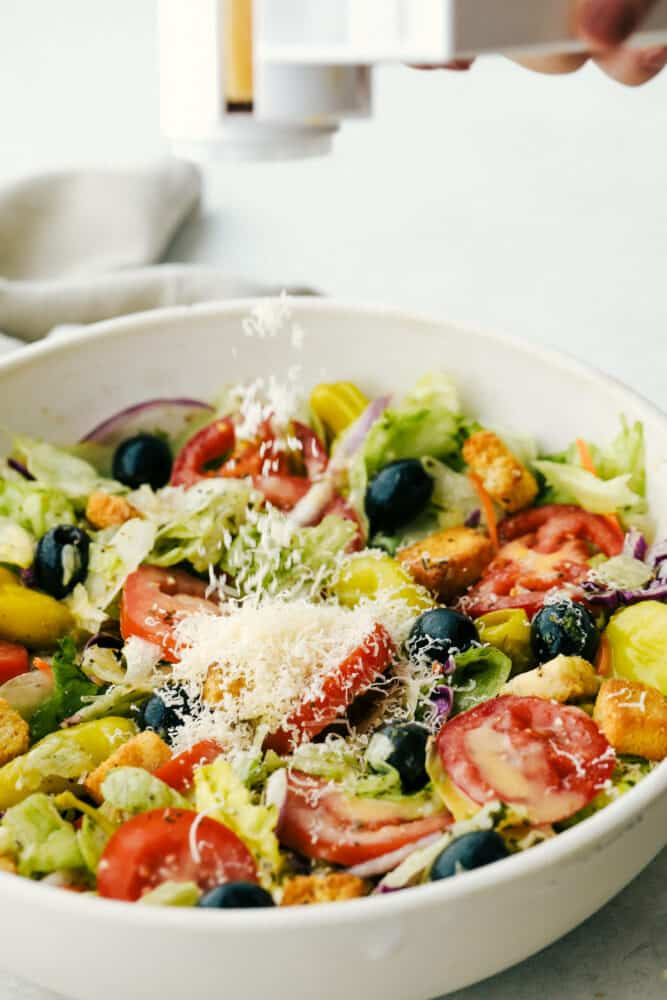 Adding Cheese to a bowl of salad.