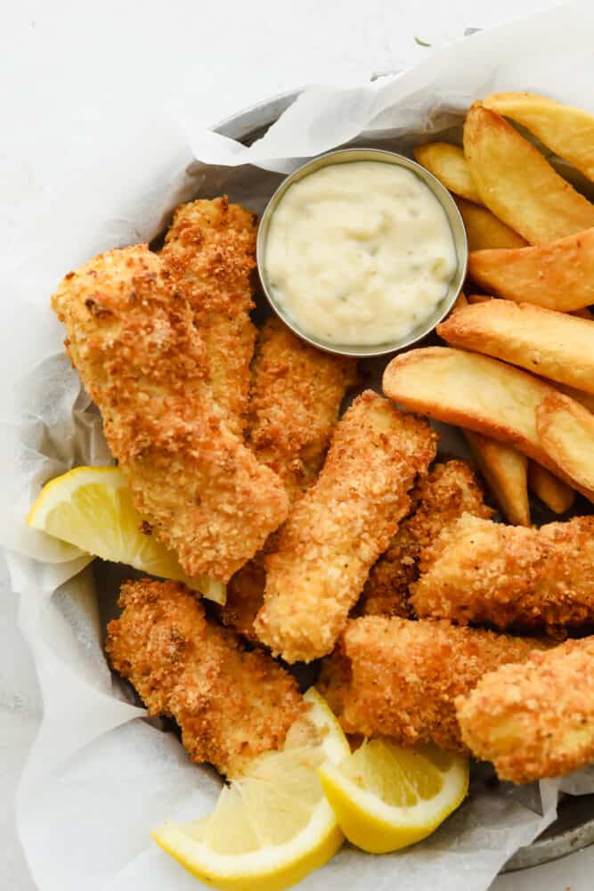 Air fryer fish sticks with french fries and tartar sauce.