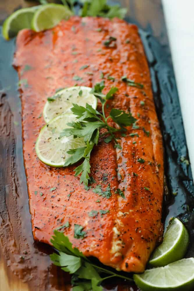 Grilled salmon on cedar plank with lime garnish.