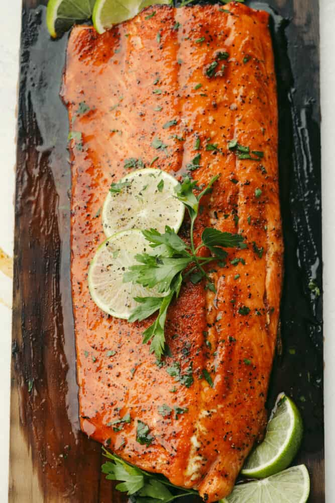 Grilled salmon on cedar plank with garnish.