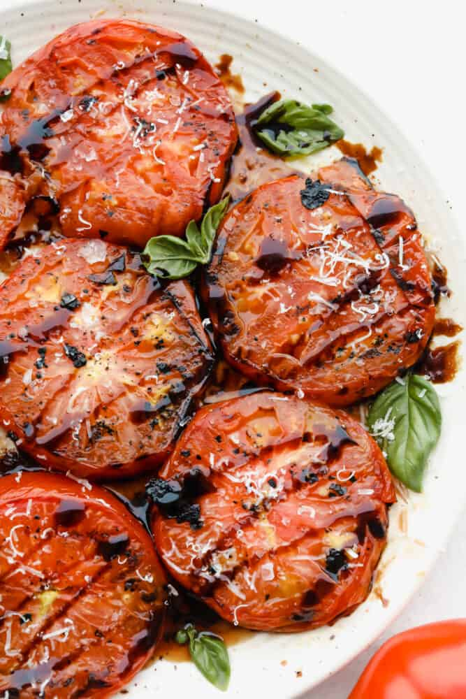 Grilled tomatoes on plate with balsamic vinegar glaze.
