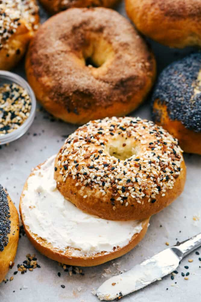 Homemade bagels with one sliced with cream cheese.