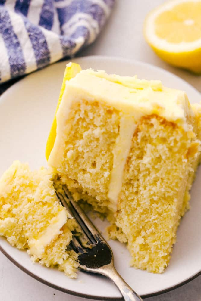 Using a fork to take a bite of the cake with lemon frosting.