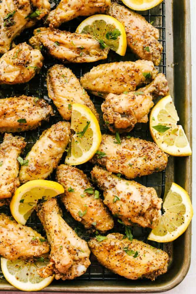 Lemon Pepper Wings on a baking rack with lemon garnish